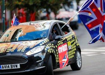 Un hombre ondea una bandera de la Unión Europea y otra británica desde un auto adornado con mensajes contra el Brexit frente a la sede de la UE en Bruselas, el 17 de octubre de 2019. Foto: Frank Augstein/AP