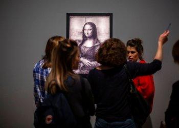 Periodistas se reúnen frente a una imagen de la Mona Lisa de Leonardo Da Vinci durante una visita al Museo del Louvre el domingo 20 de octubre del 2019, en París. Foto: Rafael Yaghobzadeh/AP