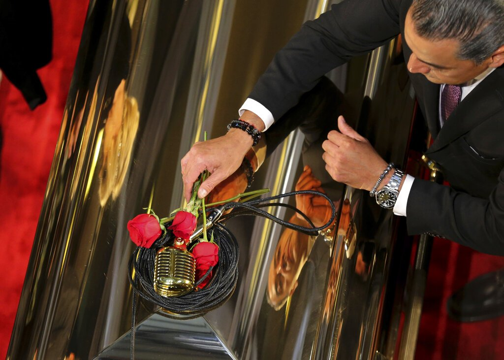 Un hombre coloca rosas rojas sobre un micrófono en el féretro del fallecido cantante mexicano José José durante una ceremonia póstuma en el Palacio de Bellas Artes el miércoles 9 de octubre de 2019. Foto: Fernando Llano / AP.
