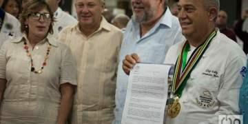 El chef Eddy Fernández (d), presidente de la Federación Culinaria de Cuba, muestra el documento que acredita a la cocina cubana como Patrimonio Cultural de la nación. Junto a él, el ministro de turismo de Cuba, Manuel Marrero (2-d) y Gladys Collazo, presidenta del Consejo Nacional de Patrimonio Cultural (i), entre otras personalidades. Foto: Otmaro Rodríguez.