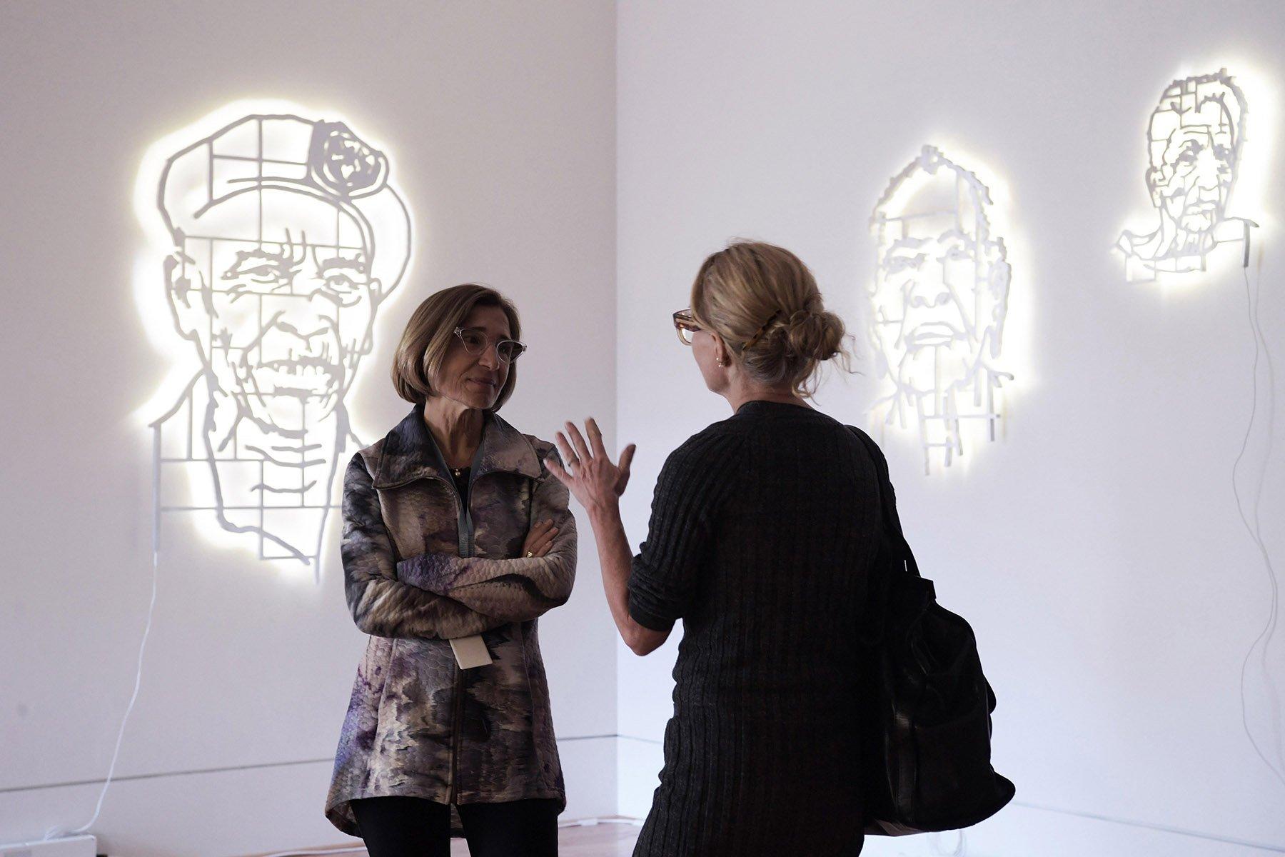 """Dos mujeres conversan frente a las obras del colectivo artístico """"Los Carpinteros"""" durante una visita a la exposición """"Cuba Va!"""" en la Phillips Collection en Washington, Estados Unidos. Foto: Lenin Nolly / EFE."""