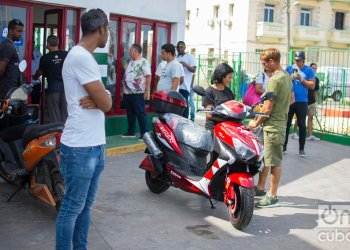 Un pareja junto una moto eléctrica comprada en el servicentro El Tángana, en La Habana, el 28 de octubre de 2019. Foto: Otmaro Rodríguez.