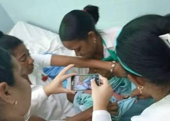 """La estomatóloga Yudelsi Céspedes amamanta a una bebé abandonada en Alamar, La Habana, junto a enfermeras del policlínico """"13 de Marzo"""". Foto: Captura de pantalla de un video publicado en Facebook."""