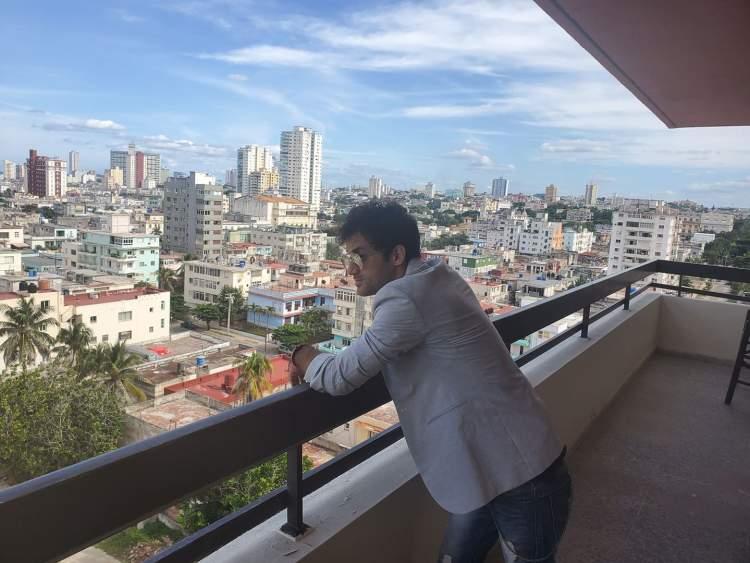 Ernesto Blanco observa la ciudad desde el balcón de la sede de OnCuba. Foto: Michel Hernández