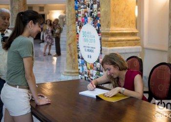 La diseñadora y fotófraga Yailin Alfaro firma un ejemplar de su libro Alicia Alonso: una mirada a su vida a través del lente, presentado este 6 de noviembre en el Gran Teatro de La Habana. Foto: Otmaro Rodríguez.