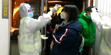 Funcionarios de salud revisan la temperatura corporal de los pasajeros que llegan de la ciudad de Wuhan al aeropuerto de Beijing, el miércoles 22 de enero de 2020. Foto: AP/Emily Wang