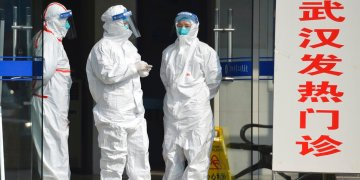 Fotografía de archivo del 28 de enero de 2020 de personal médico en trajes protectores esperando en la entrada de una clínica a que lleguen pacientes con fiebre y pacientes de Wuhan en Fuyang, en la provincia Anhui en el centro de China. Foto: Chinatopix vía AP/ Archivo