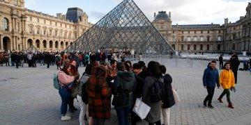 Turistas esperan y empleados en huelga se manifiestan en la entrada al Museo del Louvre, París, viernes 17 de enero de 2020. El museo estaba cerrado en medio de huelgas contra el plan del gobierno de reformar el sistema jubilatorio. (AP Foto/Francois Mori)