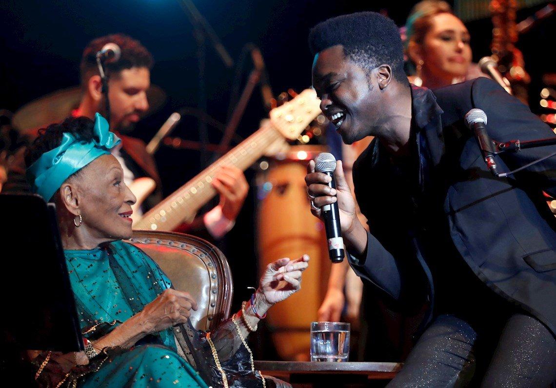 La cantante cubana Omara Portuondo junto al joven músico Cimafunk, en el concierto homenaje organizado por el músico Roberto Fonseca, durante la clausura del 35 Festival de Jazz Plaza de La Habana, el 19 de enero de 2020. Foto: Ernesto Mastrascusa / EFE.