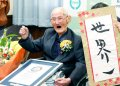 Chitetsu Watanabe, de 112 años, posa junto a un cartel que escribió tras ser condecorado como el hombre más viejo del mundo por el Guinness World Records. (Kyodo News via AP)