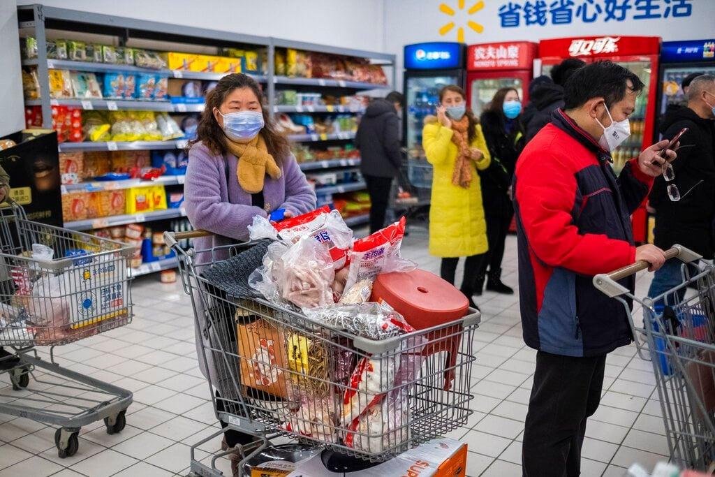 En esta foto del 22 de enero de 2020, clientes con cubrebocas hacen compras en una verdulería en Wuhan, China. Foto: AP/Arek Rataj