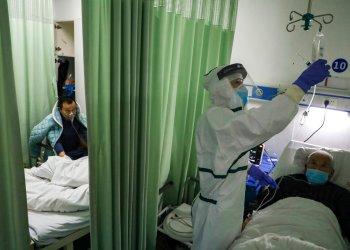 Una enfermera comprueba el estado de un paciente en un ala de aislamiento para pacientes del coronavirus 2019-nCoV en un hospital de Wuhan, en la provincia china de Hubei. Foto: Chinatopix vía AP.