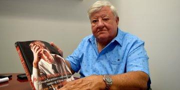 """El investigador y periodista cubano Miguel Ángel Sánchez mientras muestra su libro """"Bobby Fischer en Cuba: Sus viajes, partidas y aventuras en la tierra de Capablanca"""" durante una entrevista con Efe en Miami, Florida. Foto: Jorge I. Pérez / EFE."""