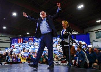 El precandidato presidencial demócrata y senador Bernie Sanders, acompañado por su esposa, Jane O'Meara Sanders, levanta los brazos durante una reunión proselitista en Essex Junction, Vermont, la noche del martes 3 de marzo de 2020. Foto: AP/Matt Rourke.