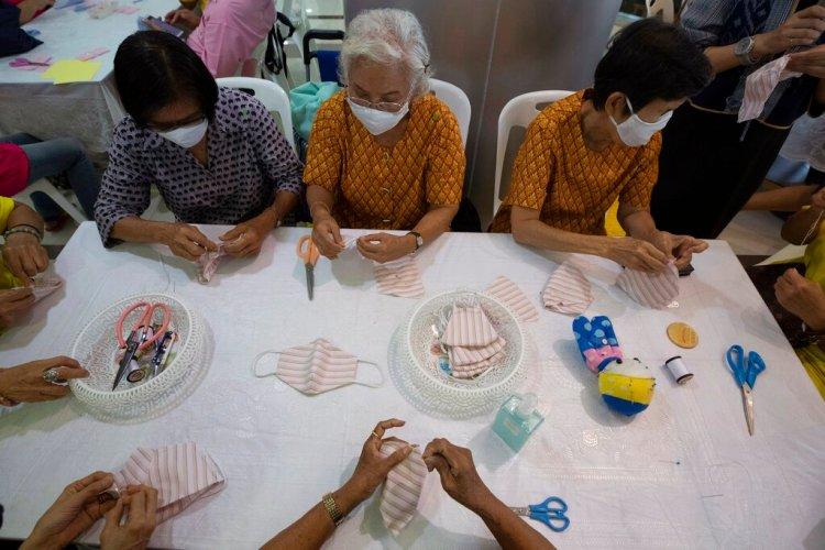 Voluntarios armando mascarillas de tela gratuitas en el Ministerio de Desarrollo Social y de Seguridad Humana en Bangkok, Tailandia, el miércoles 11 de marzo de 2020. Foto: AP/Sakchai Lalit.