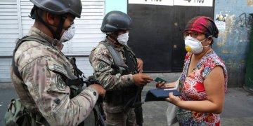 Una mujer explica a los soldados que está buscando alcohol en farmacias, antes de que la dejen continuar su camino, en el tercer día del estado de emergencia en Lima, Perú, el miércoles 18 de marzo de 2020. Foto: Martín Mejia/AP.