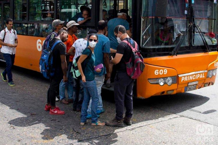 Personas se cubre parte del rostro con una mascarilla antes de subir a un ómnibus en La Habana, luego de que las autoridades sanitarias informaran sobre casos de enfermos con Covid-19 en la Isla. Foto: Otmaro Rodríguez.