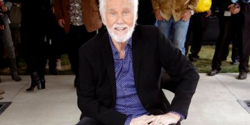 En esta imagen de archivo, tomada el 24 de octubre de 2017, Kenny Rogers posa con su estrella en el Paseo de la Fama de la Música, en Nashville, Tennessee. El cantante murió el viernes 20 de marzo de 2020. Tenía 81 años.  (AP Foto/Mark Humphrey, archivo)