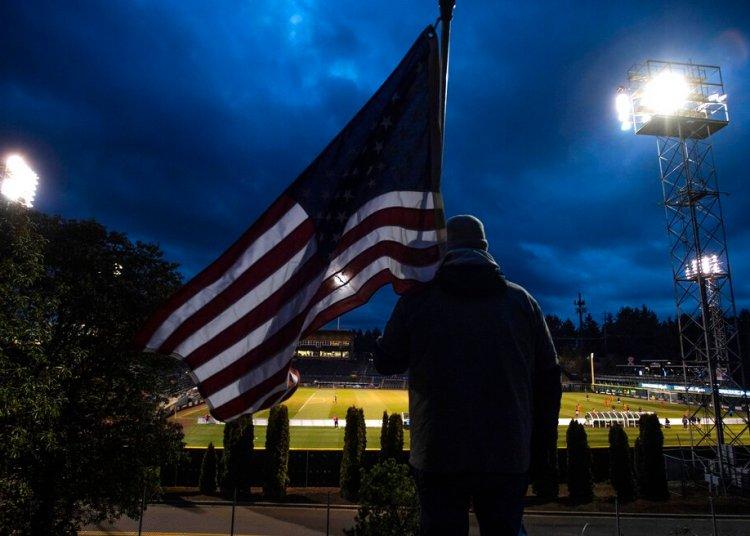 Un hombre sostiene la bandera de Estados Unidos mientras sigue un partido de la Liga de Fútbol de Estados Unidos en Tacoma, Washington. Foto: Joshua Bessex/The News Tribune via AP.