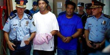 Ronaldinho y su hermano Roberto de Assis Moreira llevados por la policía a declarar ante una jueza de Asunción el 7 de marzo del 2020. Los dos fueron detenidos por ingresar a Paraguay con pasaportes falsos. Foto: Jorge Sáenz/AP.