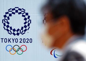 Un hombre con una máscara protectora pasa junto al logo de los juegos olímpicos Tokio 2020 el jueves, 2 de abril del 2020. Foto: AP/Eugene Hoshiko.