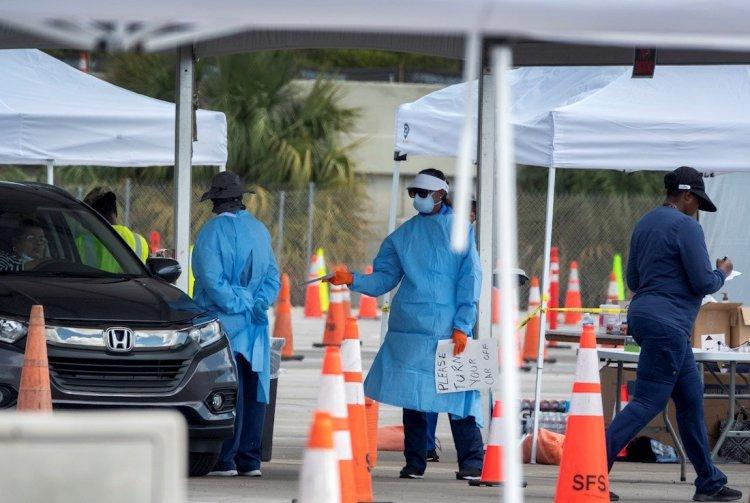 Los miembros de la Guardia Nacional usan equipo de protección mientras conducen hisopos nasales para pruebas de coronavirus en una ubicación de prueba en el estacionamiento del estadio Super Bowl de Hard Rock Cafe Miami, en Miami. Foto: Cristóbal Herrera/EFE/EPA.