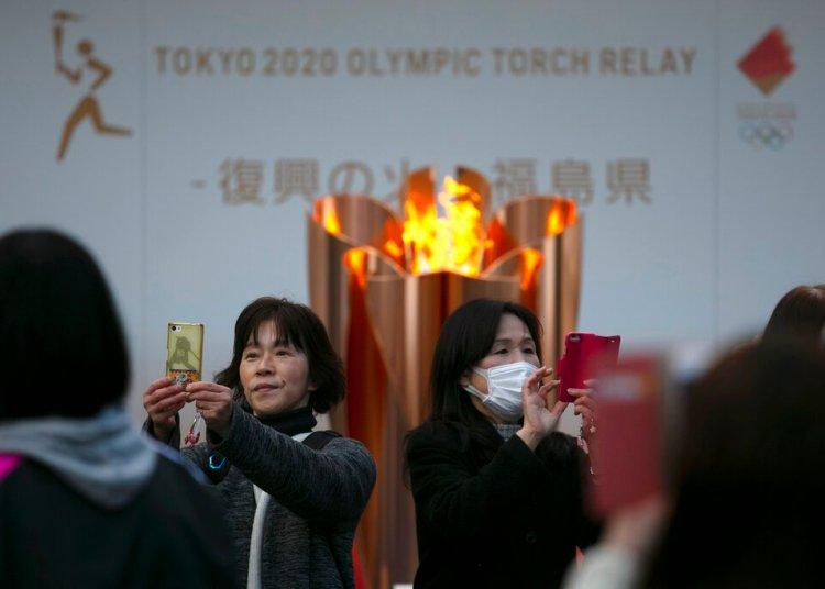 Dos mujeres se toman fotografías delante de la llama olímpica durante una ceremonia en Fukushima, Japón, en marzo de 2020. Foto/Jae C. Hong / AP / Archivo.