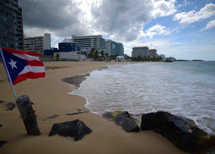 Una bandera puertorriqueña ondea en una playa vacía el 21 de mayo de 2020 en San Juan. Foto: Carlos Giusti/AP.