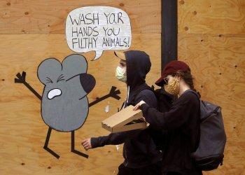 Un hombre y una mujer con mascarillas pasan junto a un mural que recuerda a la gente que se lave las manos, en una tienda protegida por tablones en San Francisco.  Foto: Jeff Chiu / AP