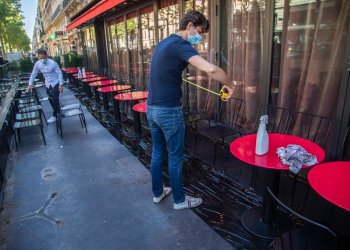 Pierre-Antoine Boureau con una cinta métrica instala las mesas en la terraza de un cadé en París, 1 de junio de 2020. Foto: Michel Euler/AP