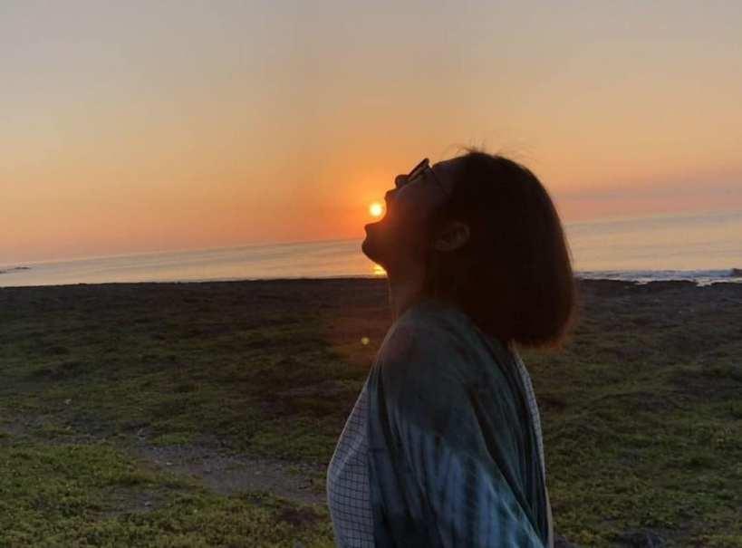 jeune femme la bouche ouverte devant un coucher de soleil