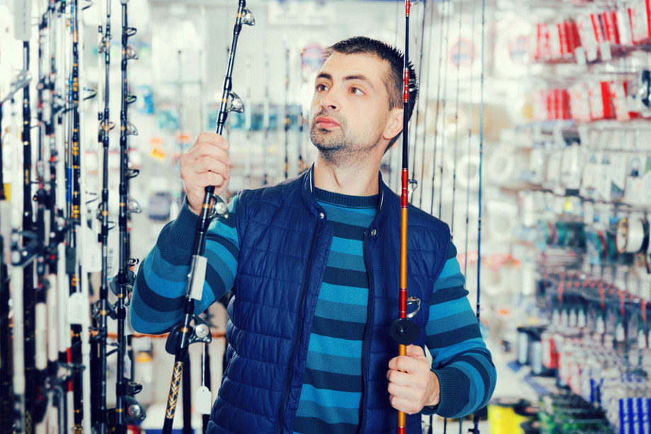 Man Looks At Fishing Rods In Store