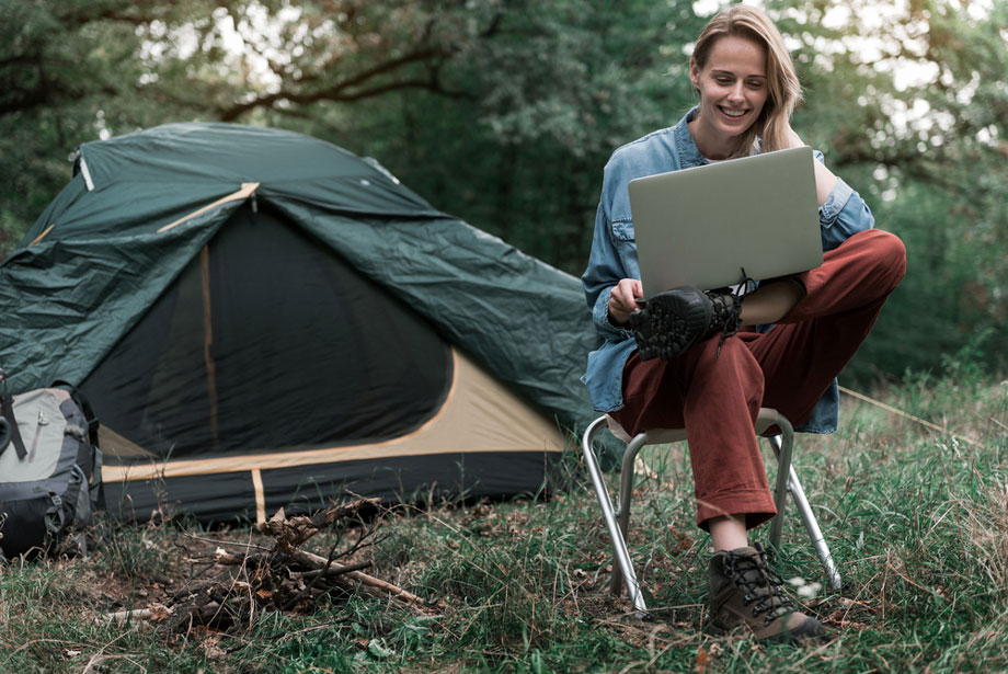Woman Uses Laptop Online While Camping