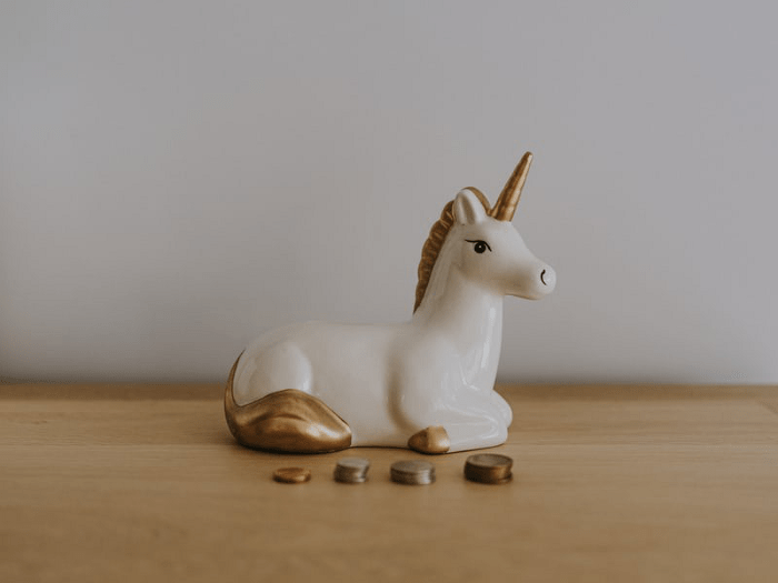 A white ceramic unicorn on a table with stacks of coins in front of it