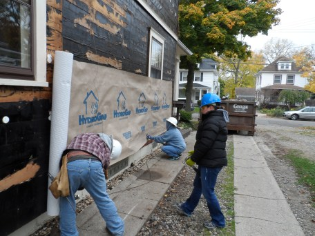 Volunteers nail insulation on a Habitat house