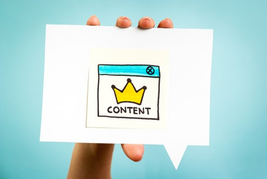 """Image of hand holding up a sign that has an image of a golden crown and the word """"content"""" underneath"""