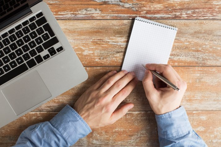 Image of Caucasian male taking notes on a notepad with a laptop beside him