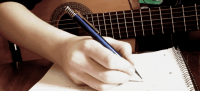 A person writing down song lyrics.