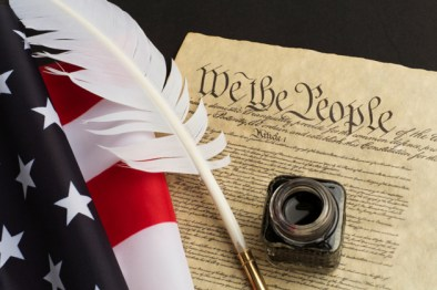 Picture of the Declaration of Independence with a feather quill, an inkwell, and the American flag along with it
