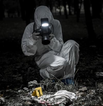 Crime scene photographer taking photos of the evidence
