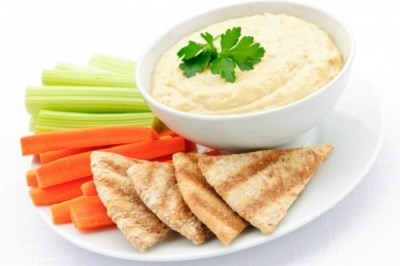 Plate with carrot, celery, pita and hummus on the side