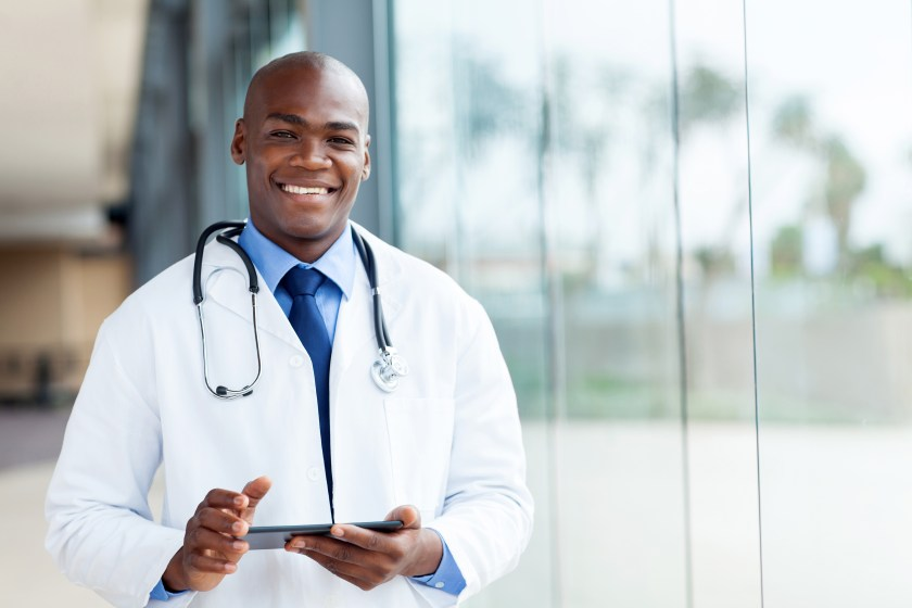 Image of a Smiliing African-American Doctor Holding A Tablet