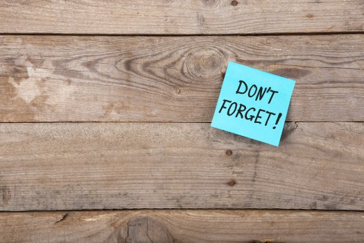 "sticky note on wooden wall saying ""don't forget"""