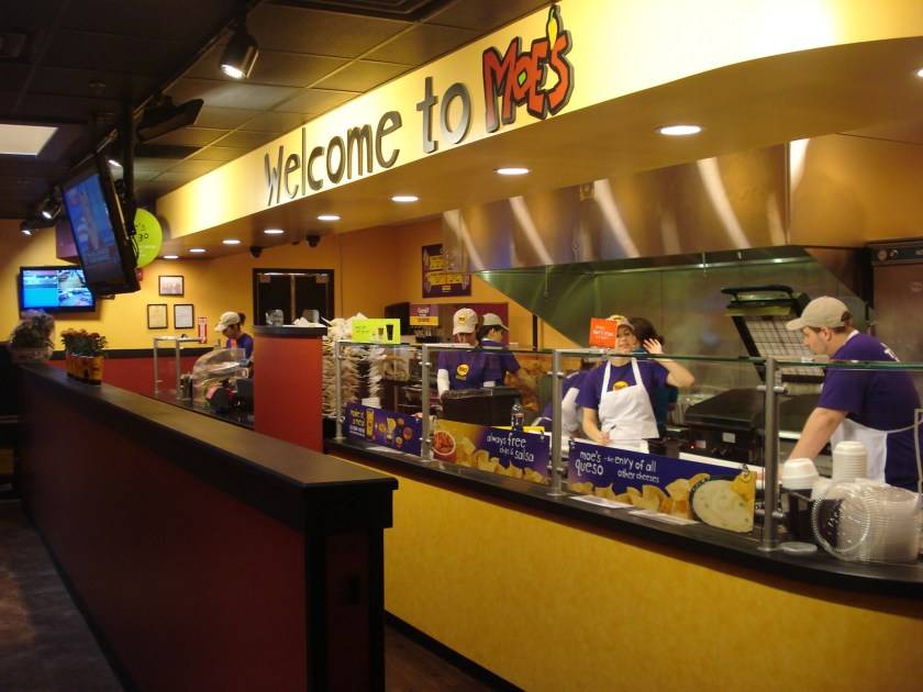 Workers at Moe's Southwestern Grill preparing meals for their customers