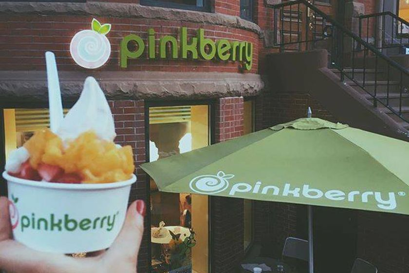 A hand holding a cup of ice cream outside Pinkberry