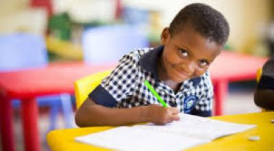 A child writing. He is looking at the camera smiling
