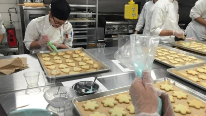 picture of a student baker decorating cookies.