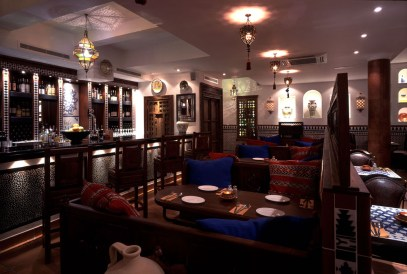 the inside of the restaurant with chairs and tables