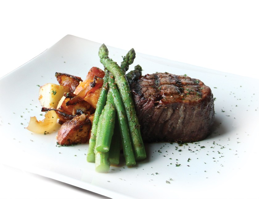 a steak with potatoes and asparagus