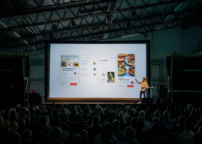 man making a presentation on a big screen to a dimly lit audience